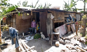 Two girls wait outside their house in an impoverished village in Bali