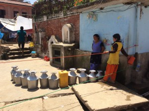 Women line up for drinking water in Bungamati. Temporary shelters can be seen on the left of the picture. (Image Credit: BNMT)